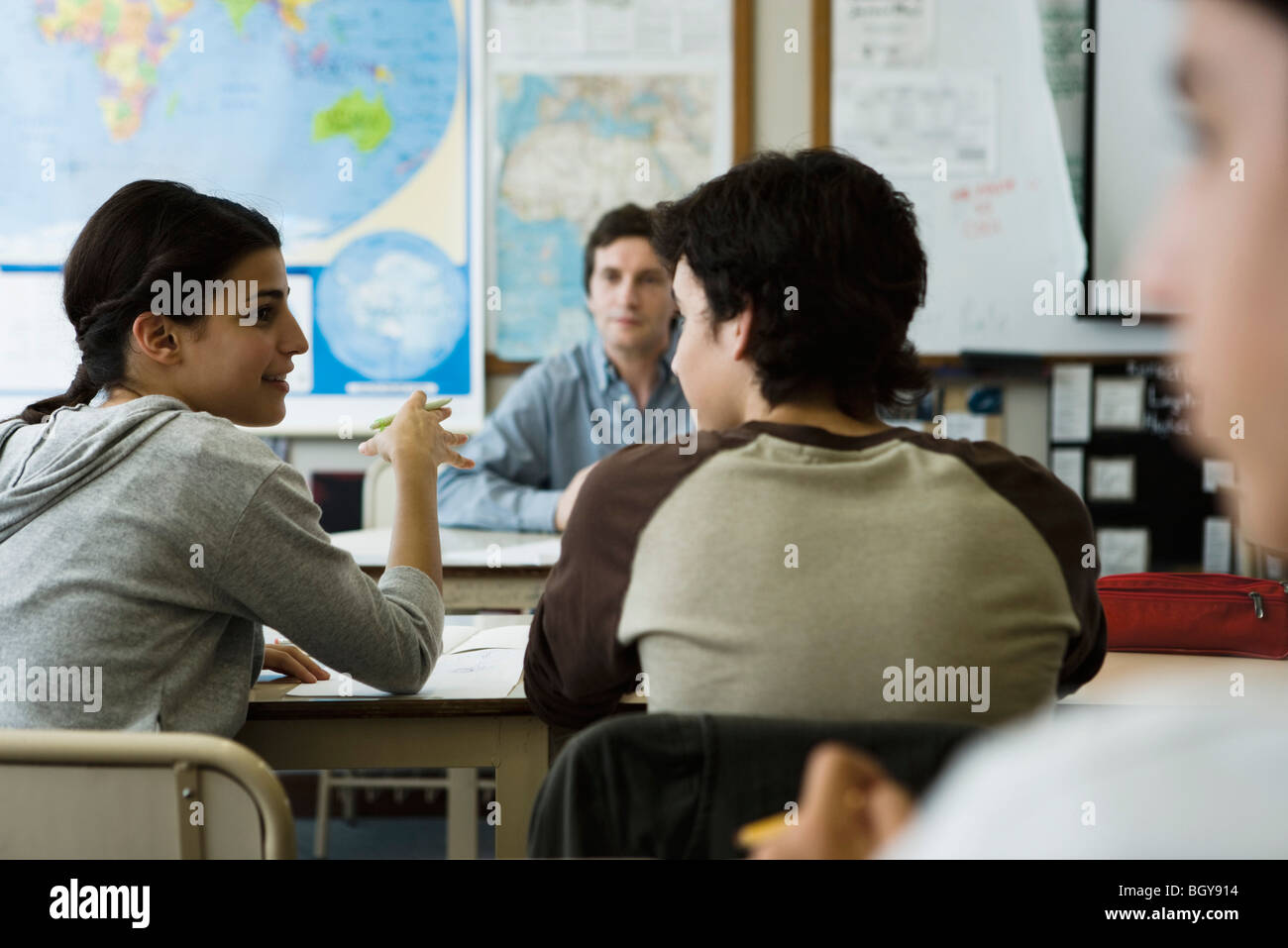 High school student speaking with classmate in class - Stock Image