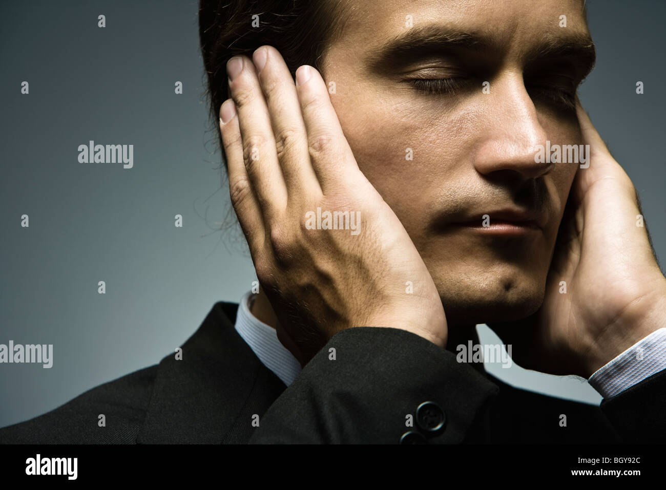 Man with hands held over ears and eyes closed Stock Photo