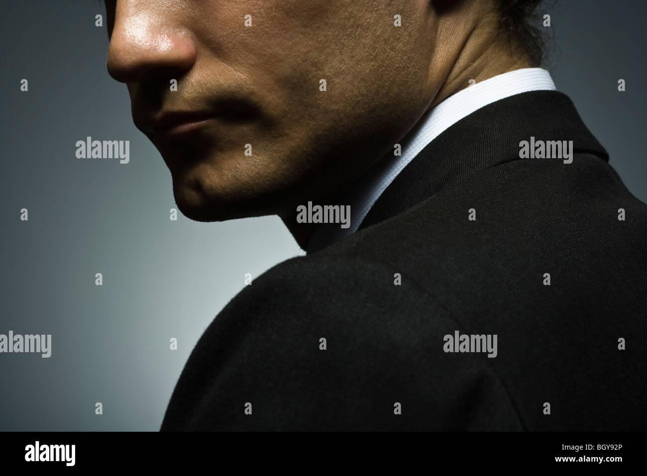Man looking over shoulder with suspicion - Stock Image