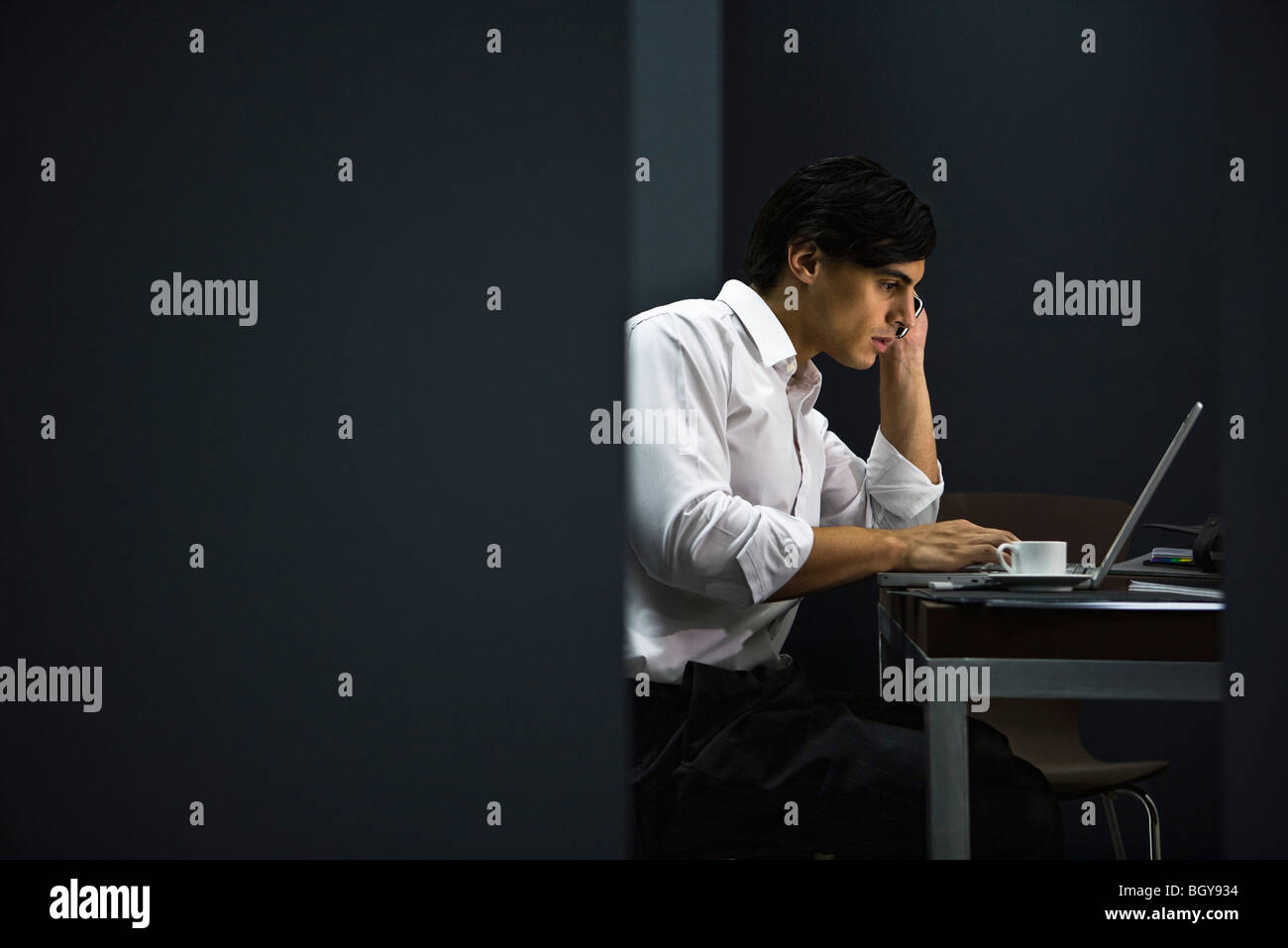 Man in office working late - Stock Image