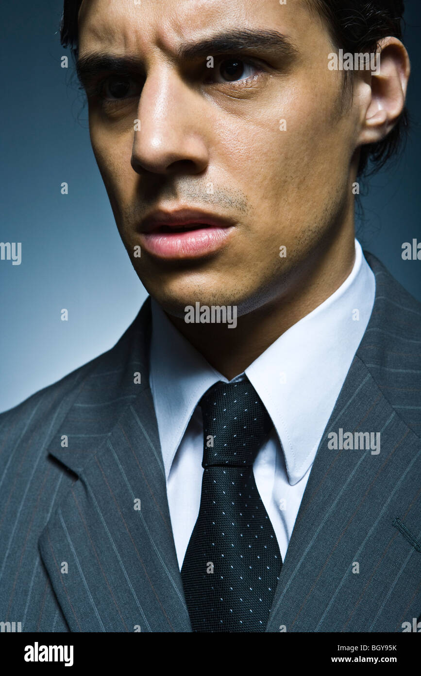 Businessman looking away angrily - Stock Image