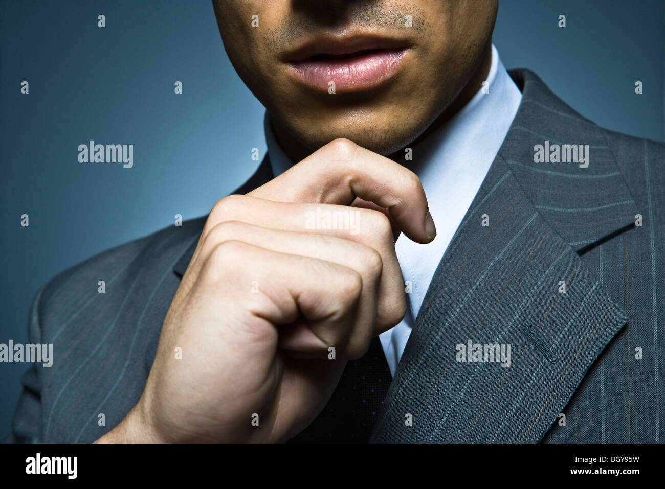 Businessman with hand under chin, cropped portrait - Stock Image