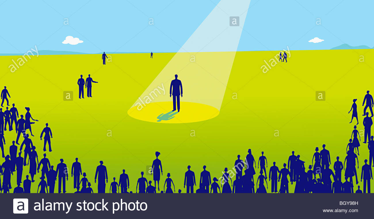 Audience watching man standing in spotlight - Stock Image