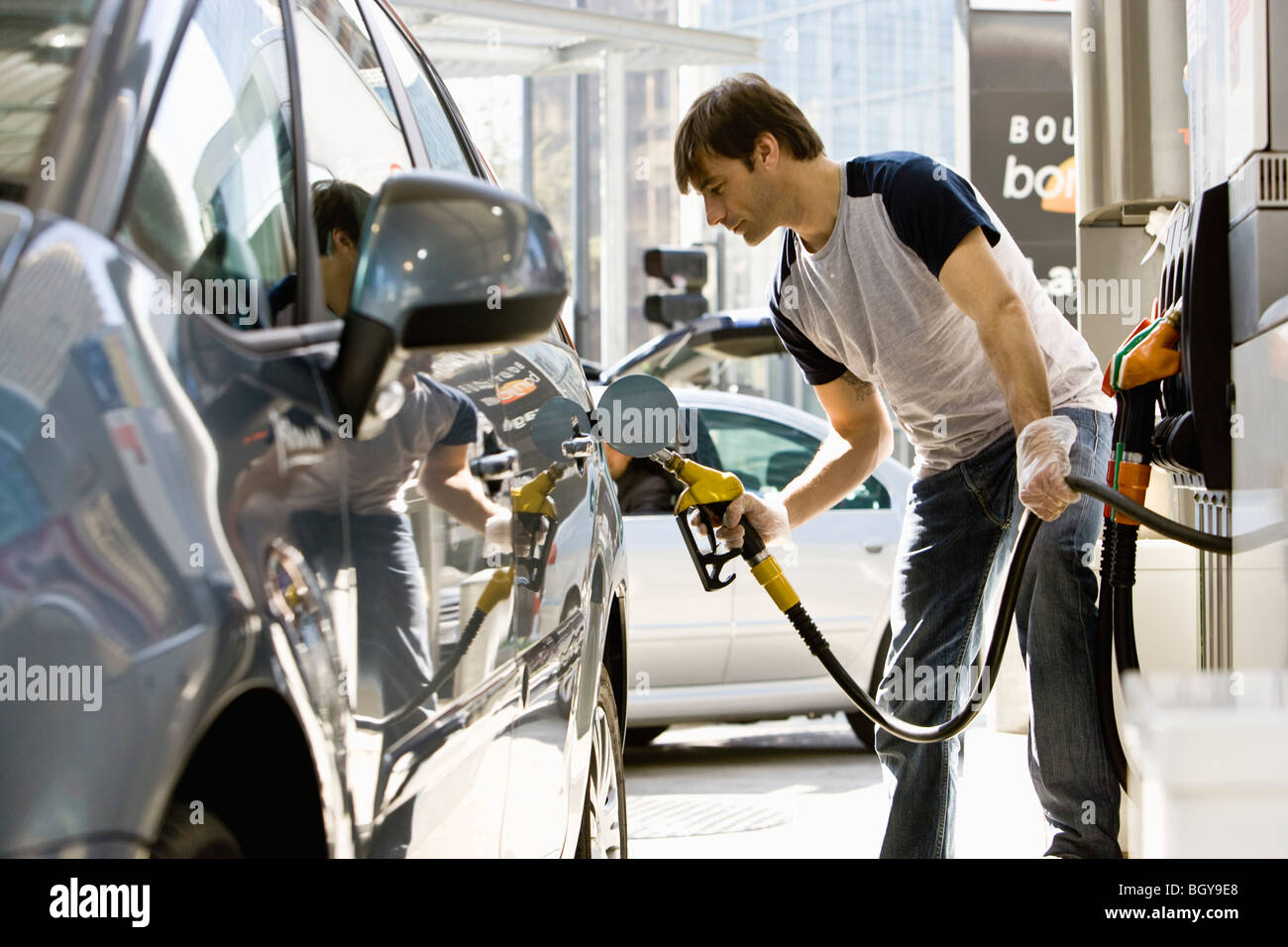Man refueling vehicle at gas station - Stock Image