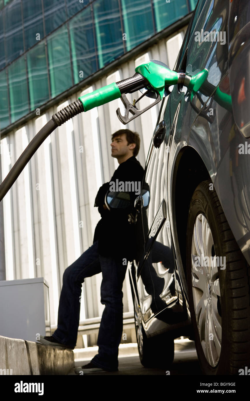 Man at gas station leaning against car waiting to finish refueling - Stock Image