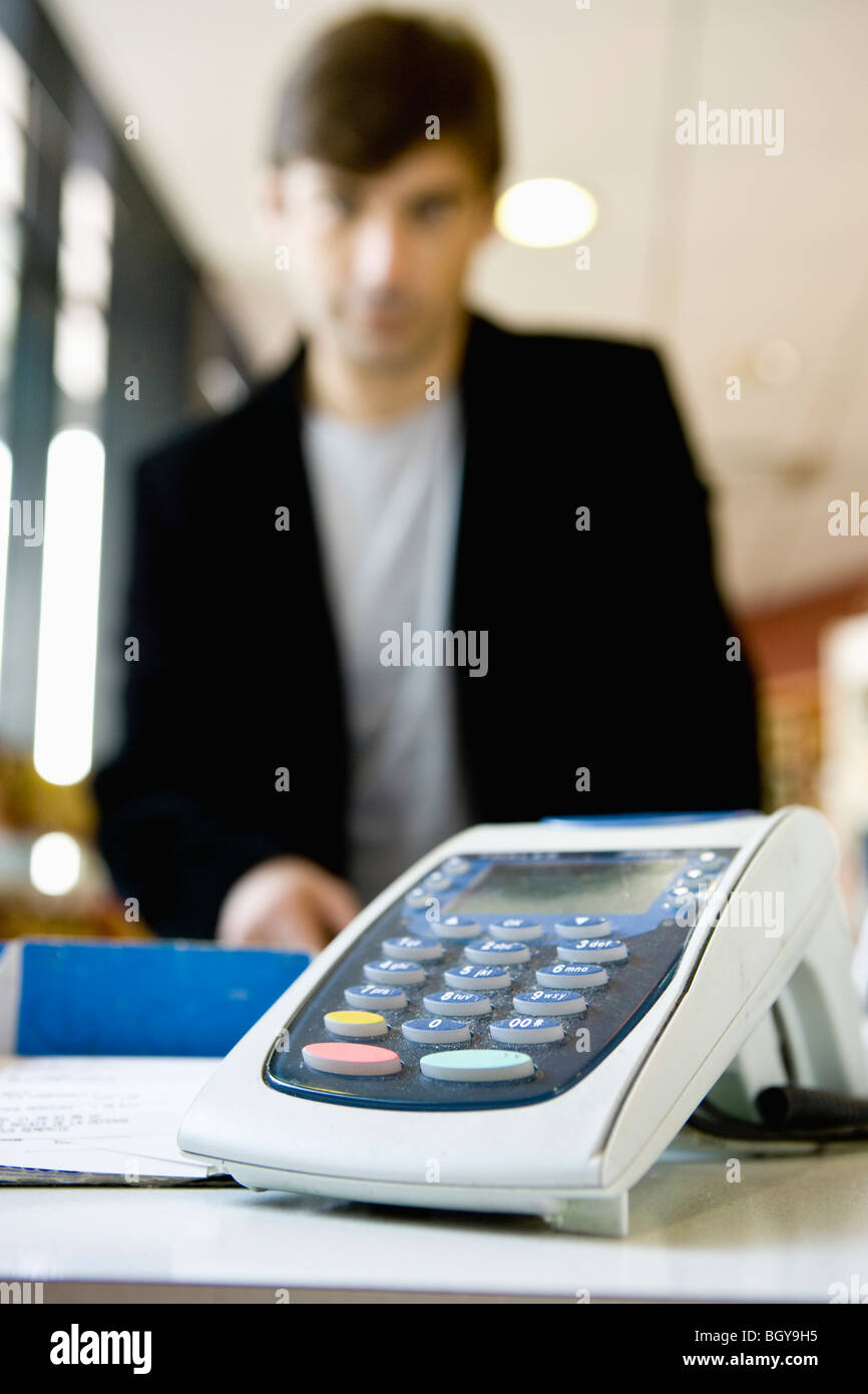 Credit card reader on checkout counter, customer in background Stock Photo