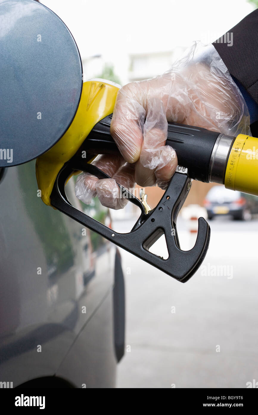 Refueling vehicle, wearing disposable glove - Stock Image