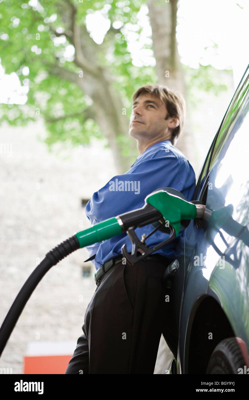 Well-dressed man refueling vehicle at gas station - Stock Image