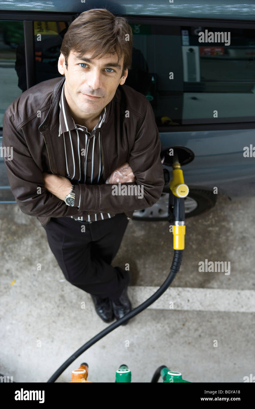 Man standing with arms folded refueling vehicle at gas station - Stock Image