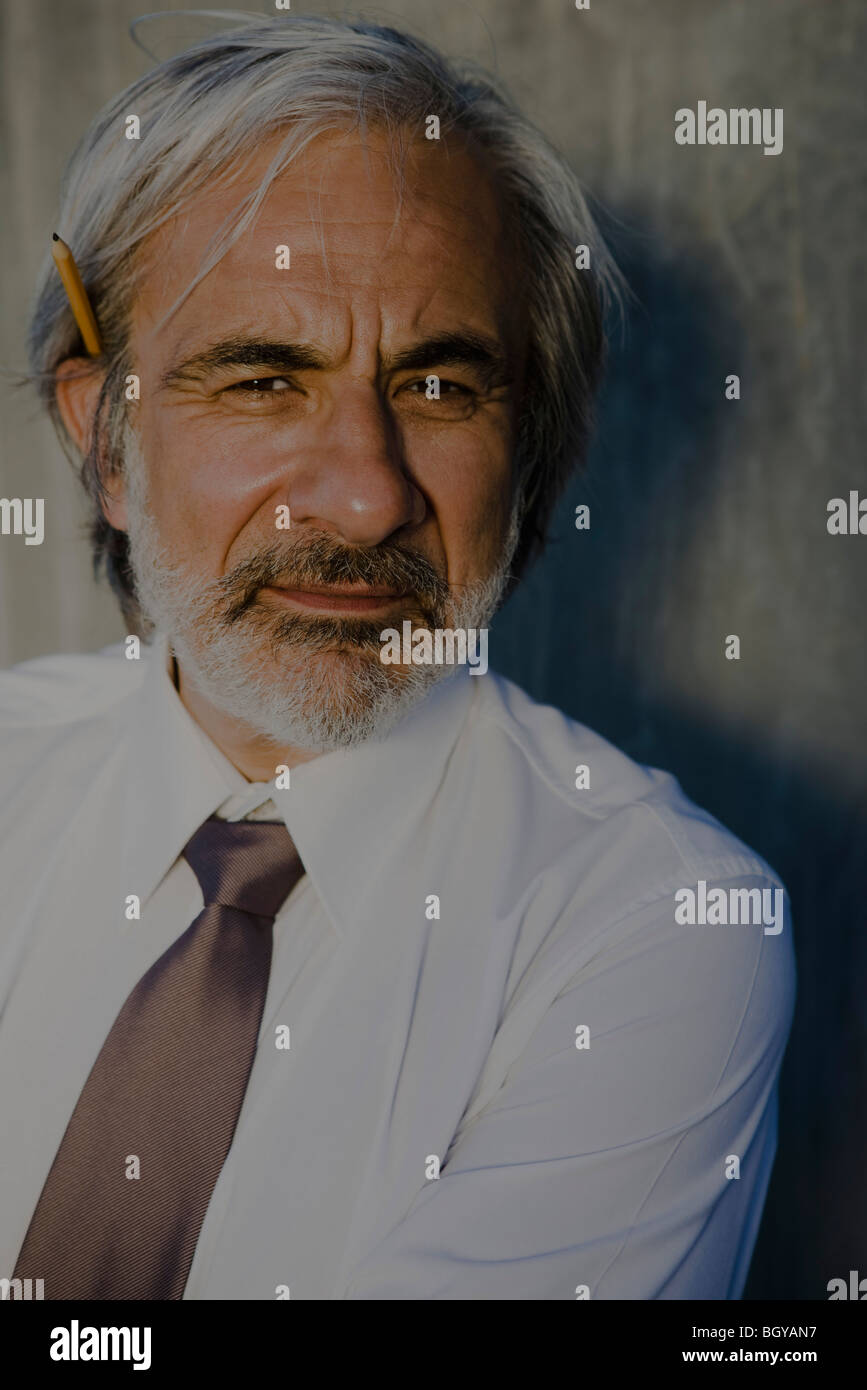 Businessman with pencil tucked behind one ear, portrait - Stock Image