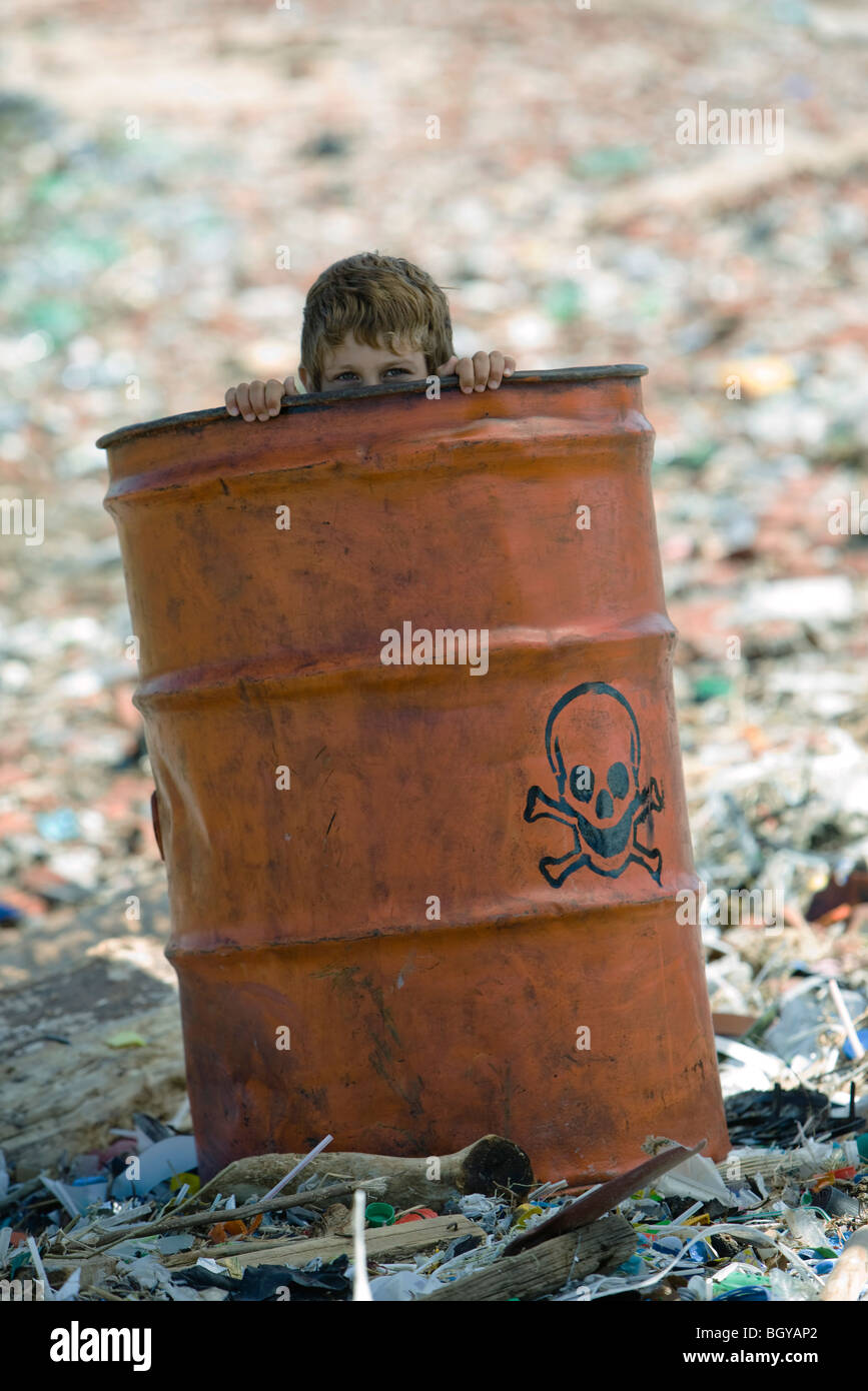 Child peeking over edge of metal barrel marked with skull and bones, surrounded by landfill Stock Photo