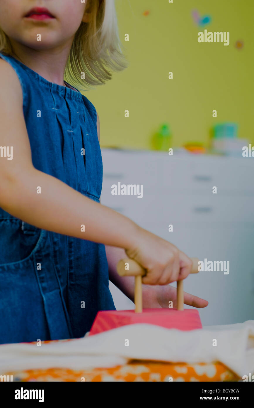 Little girl playing with toy iron - Stock Image