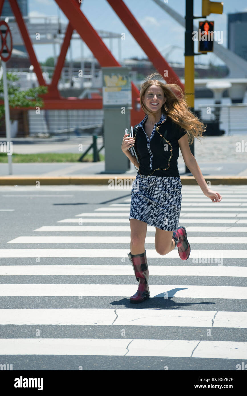 Young woman running across crosswalk while walk signal is red - Stock Image