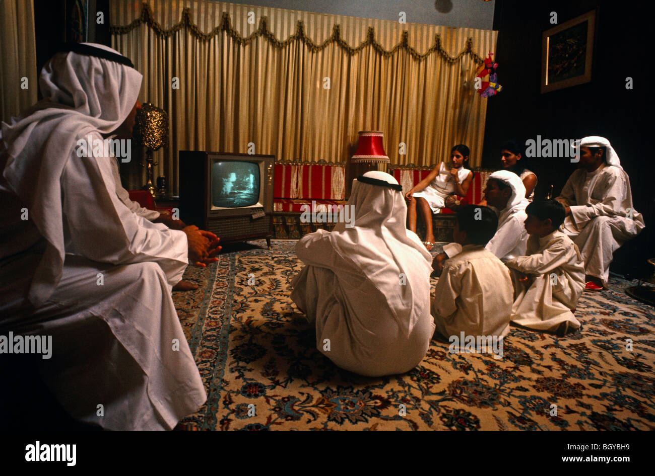 July 20, 1969.  Apollo landing of a man on the moon viewed on television by a family in Kuwait.  Arab men and women - Stock Image