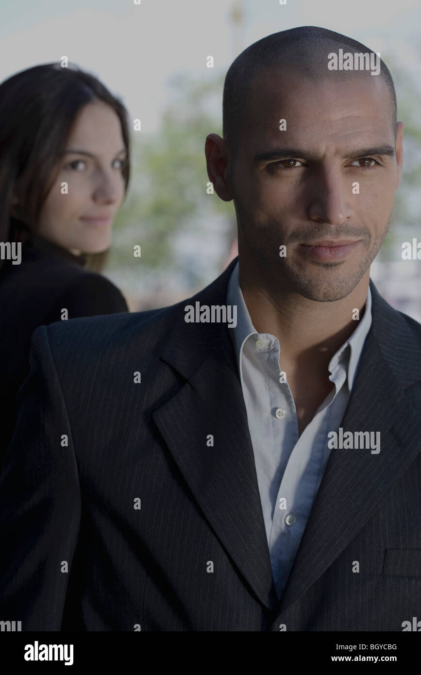 Woman looking over shoulder at well-dressed man in foreground - Stock Image
