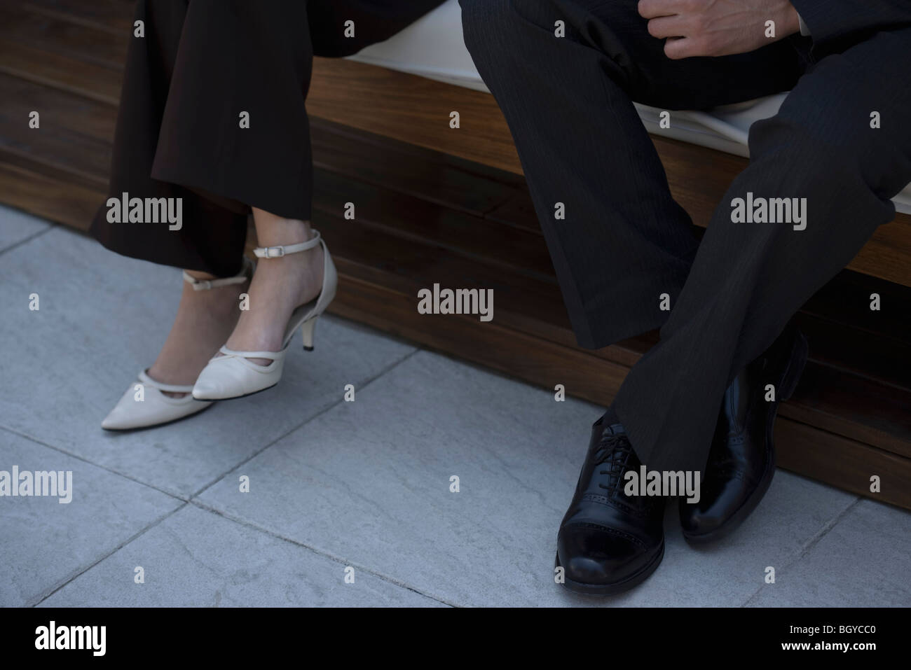 Man and woman sitting on bench indoors, low section - Stock Image