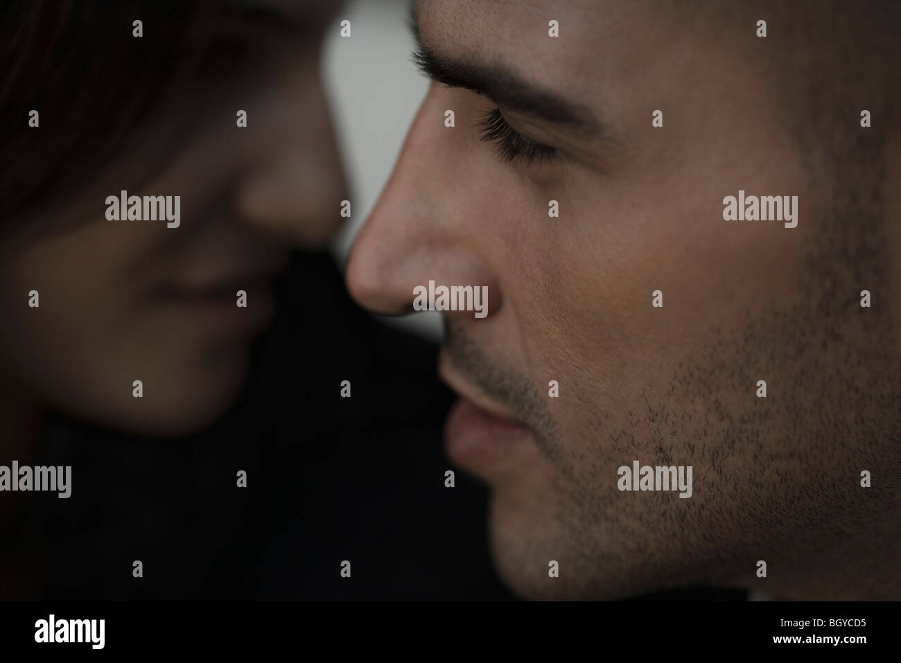 Couple face to face, focus on man's profile - Stock Image