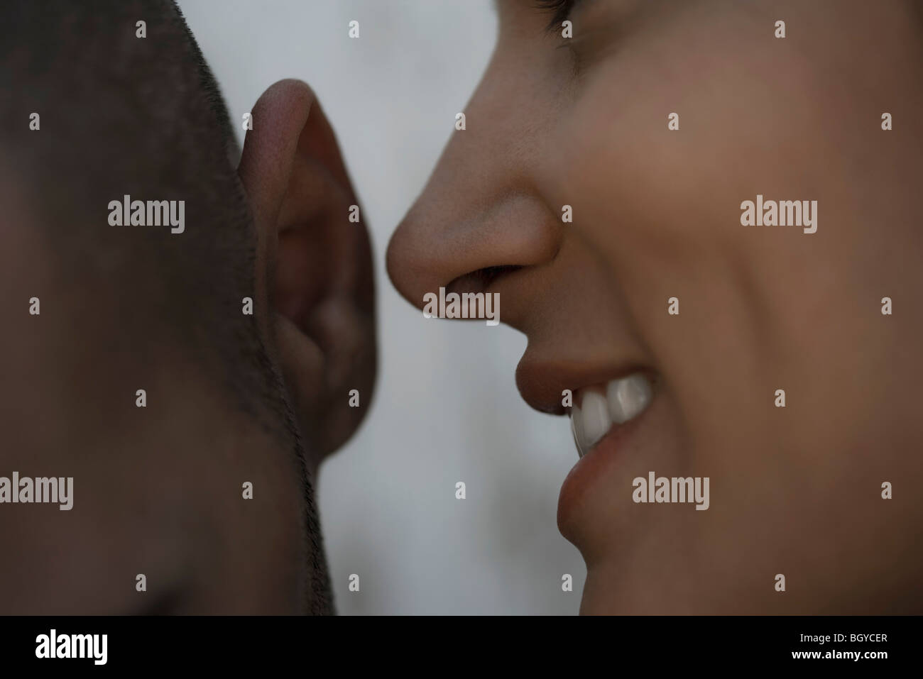 Woman whispering into man's ear, close-up - Stock Image
