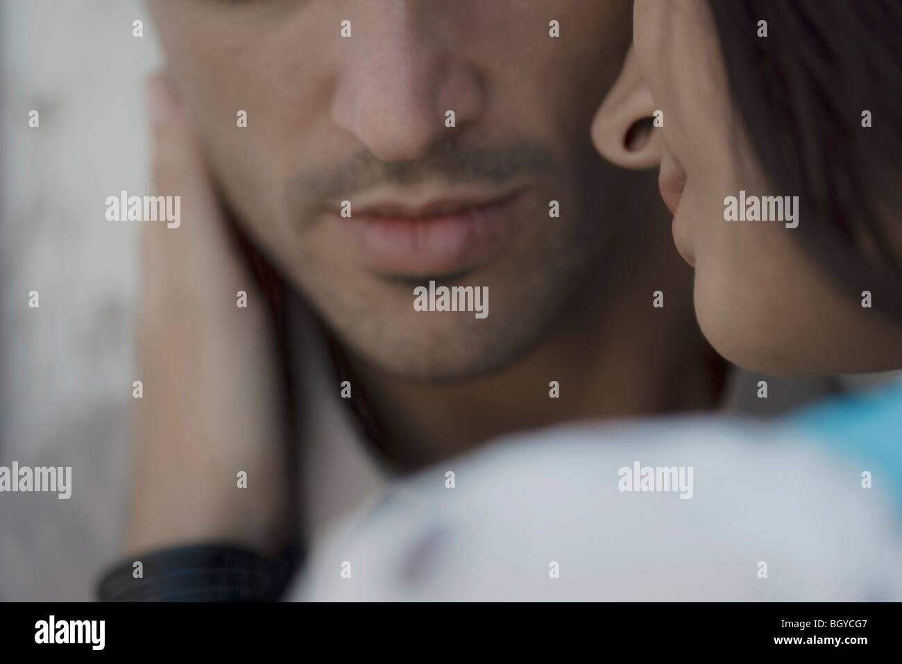 Couple close together, woman's hand caressing man's face - Stock Image