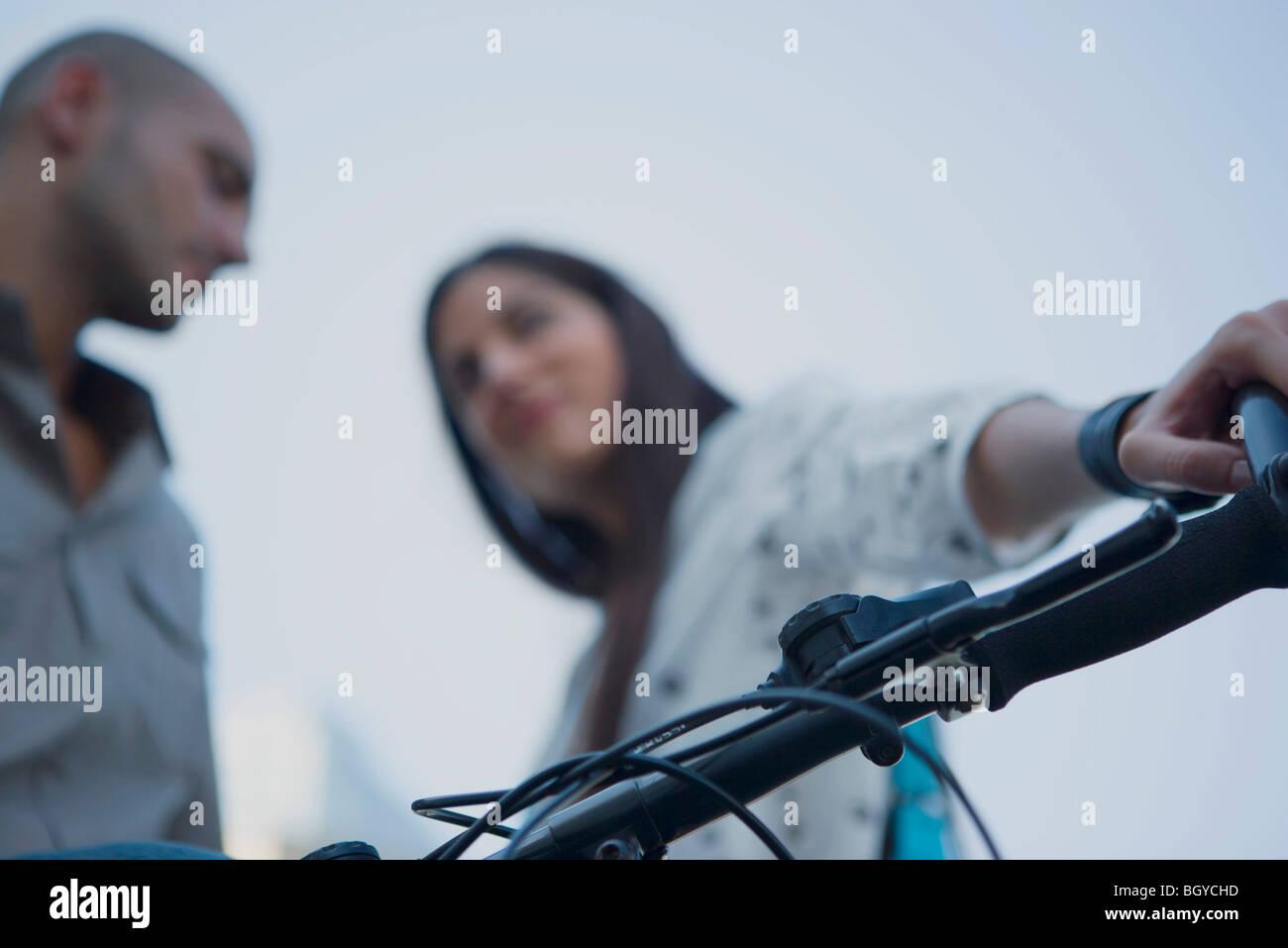 Man and woman having conversation, woman holding bike handlebar - Stock Image