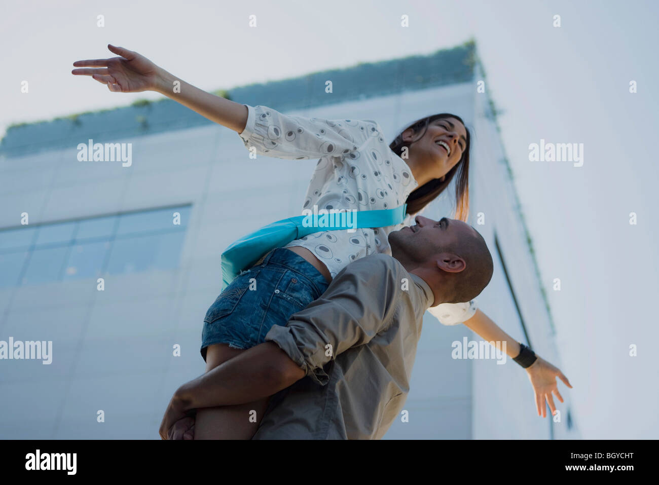 Man lifting woman in air, woman's arms outstretched - Stock Image