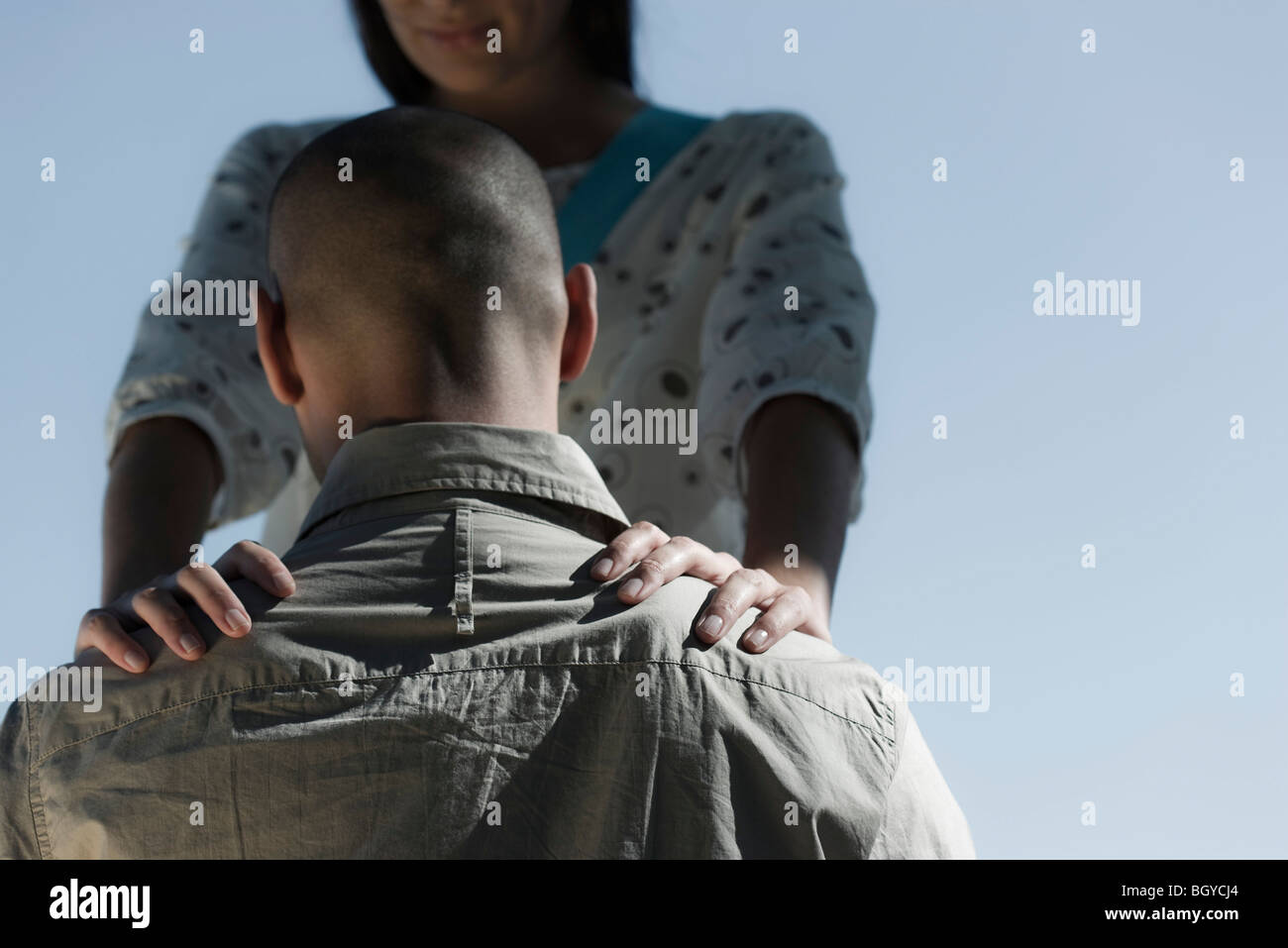 Man with head lowered, woman placing hands on his shoulders - Stock Image