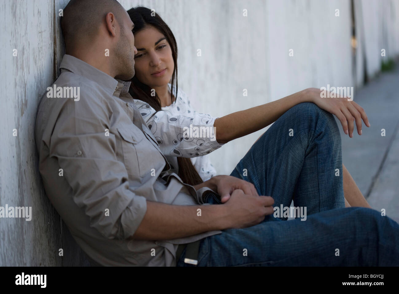 Young couple sitting side by side on ground, leaning against wall having conversation - Stock Image