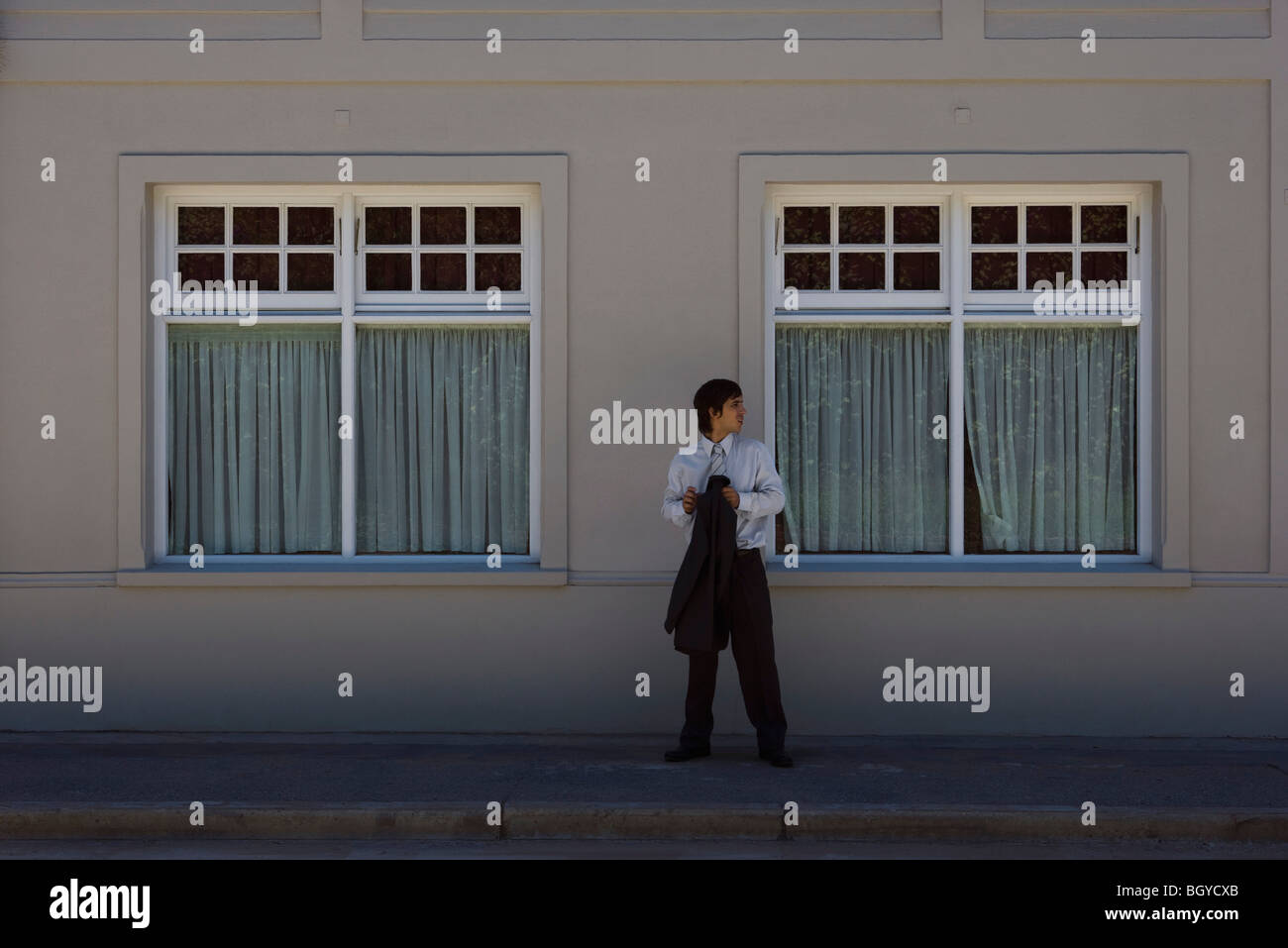 Young man standing on sidewalk, looking over shoulder - Stock Image