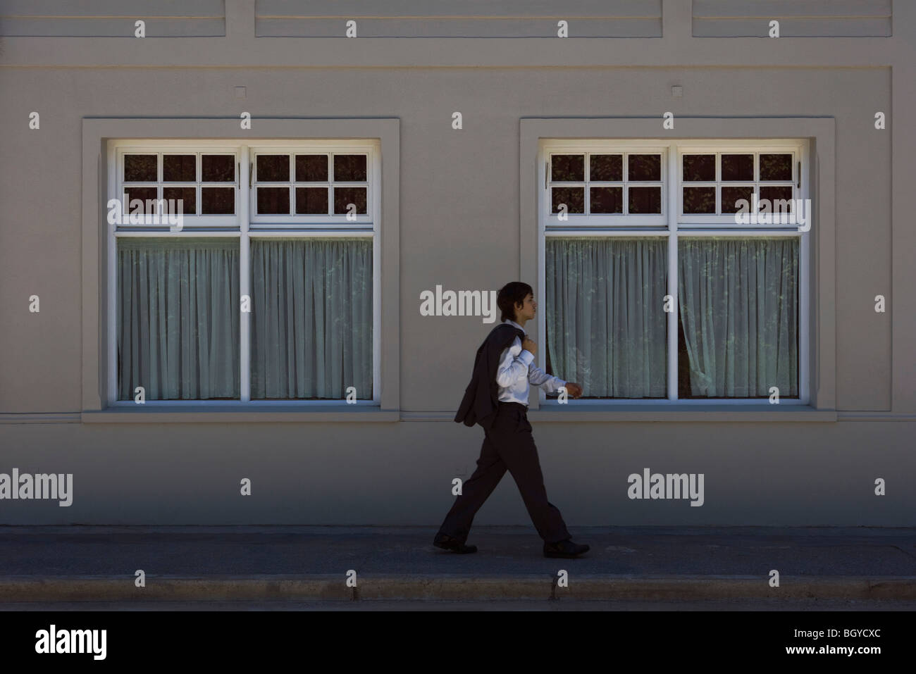 Young man in business attire walking on sidewalk, side view - Stock Image