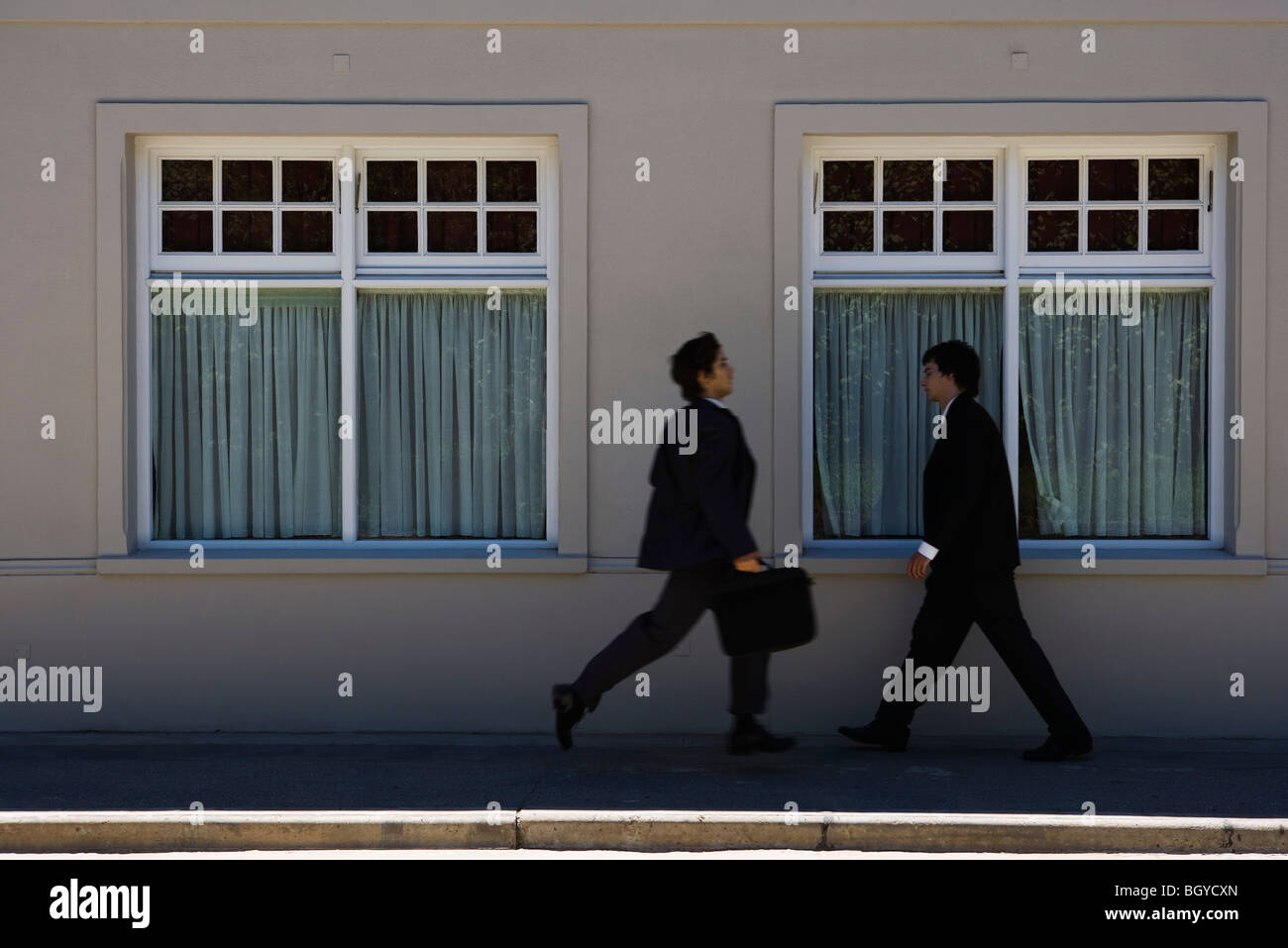 Two young businessmen hurrying toward each other on sidewalk - Stock Image