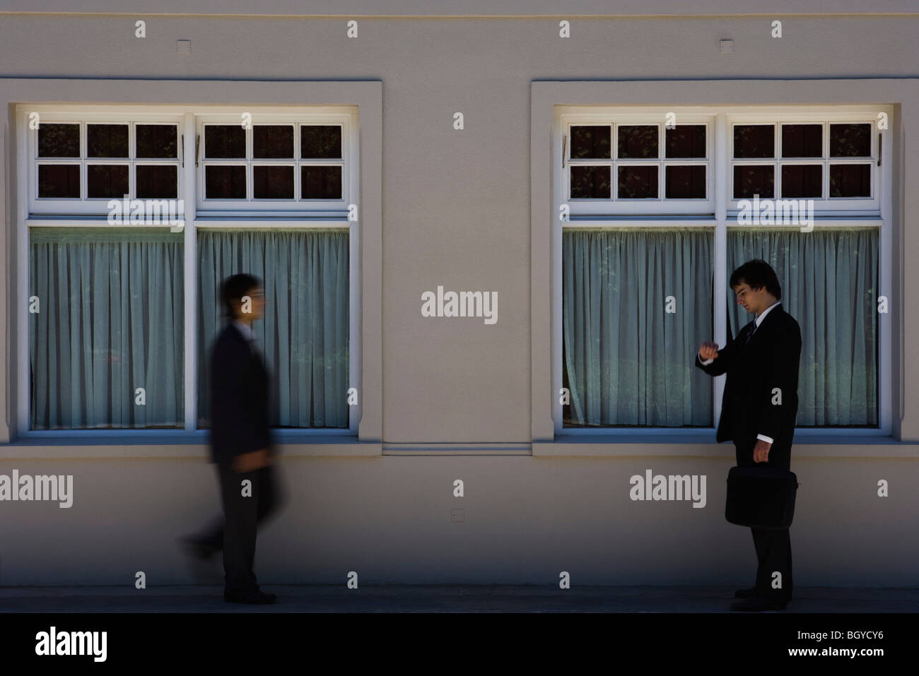 Young businessman standing on sidewalk, checking time as another man approaches - Stock Image