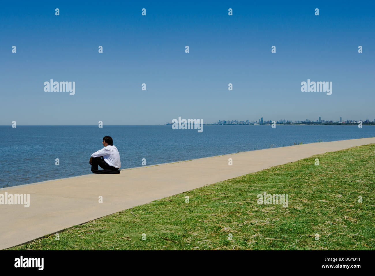 Man sitting beside sea, looking toward horizon - Stock Image