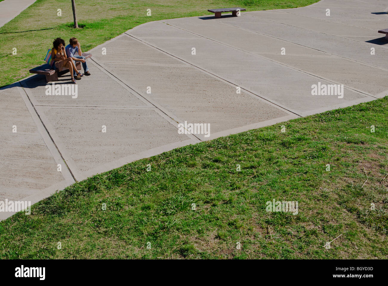 Young couple sitting on park bench, high angle view Stock Photo