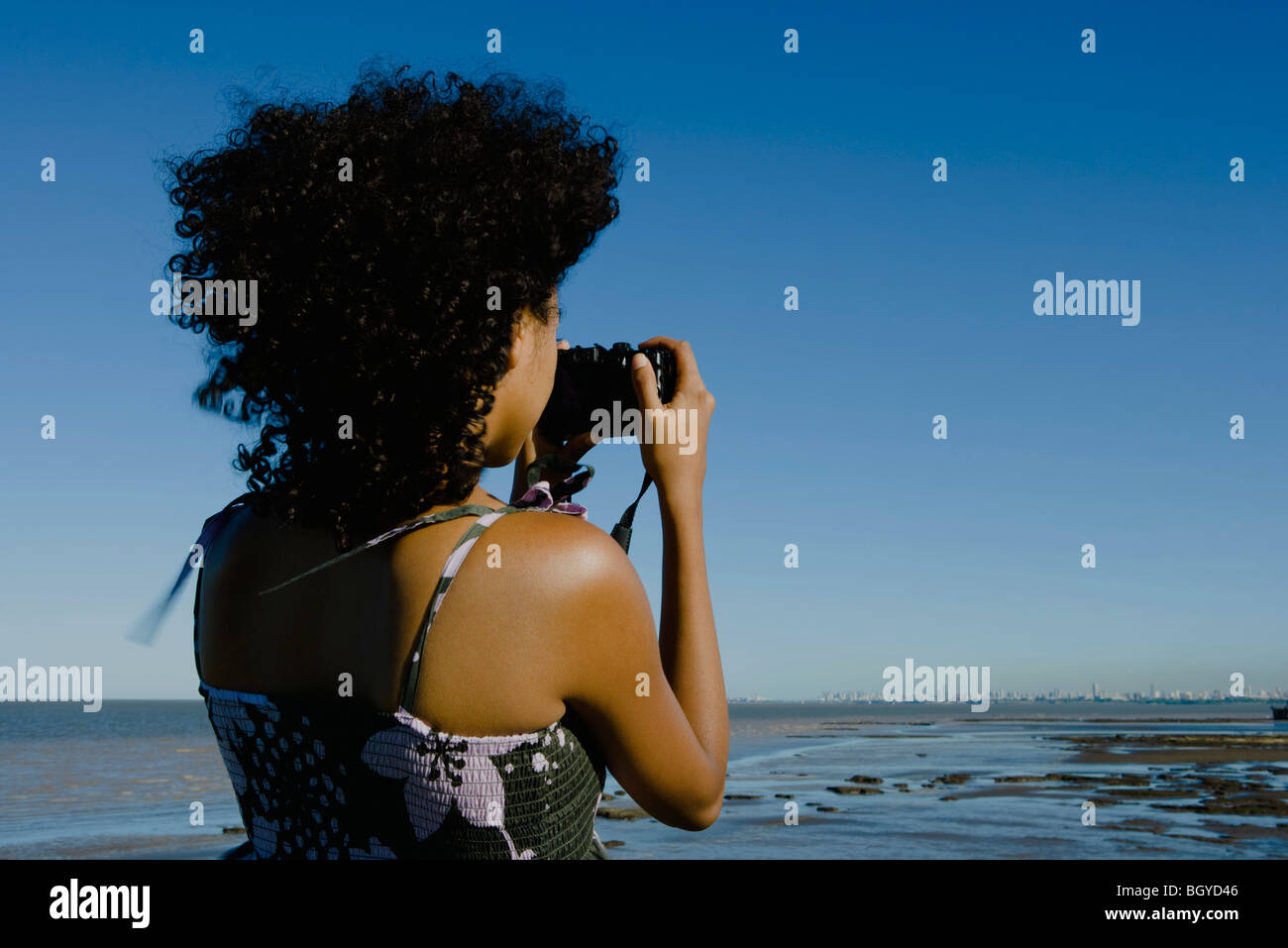 Young woman photographing coast with camera, rear view - Stock Image