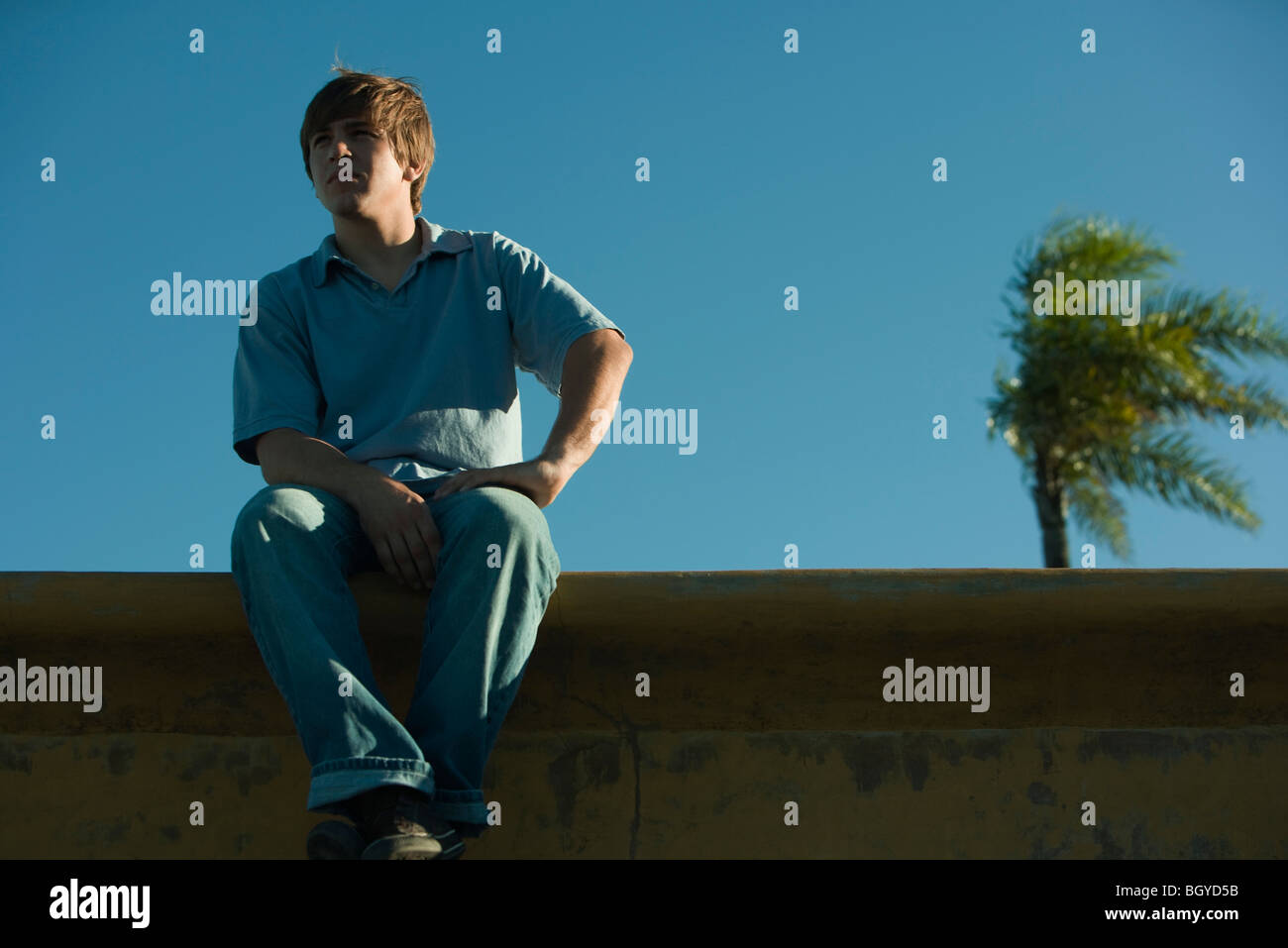 Young man sitting on ledge, looking away - Stock Image