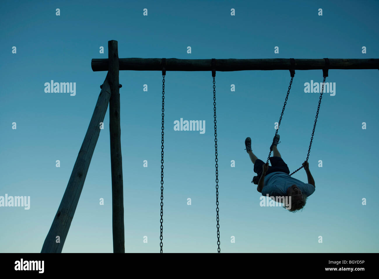 Young man swinging on swing set, backlit - Stock Image