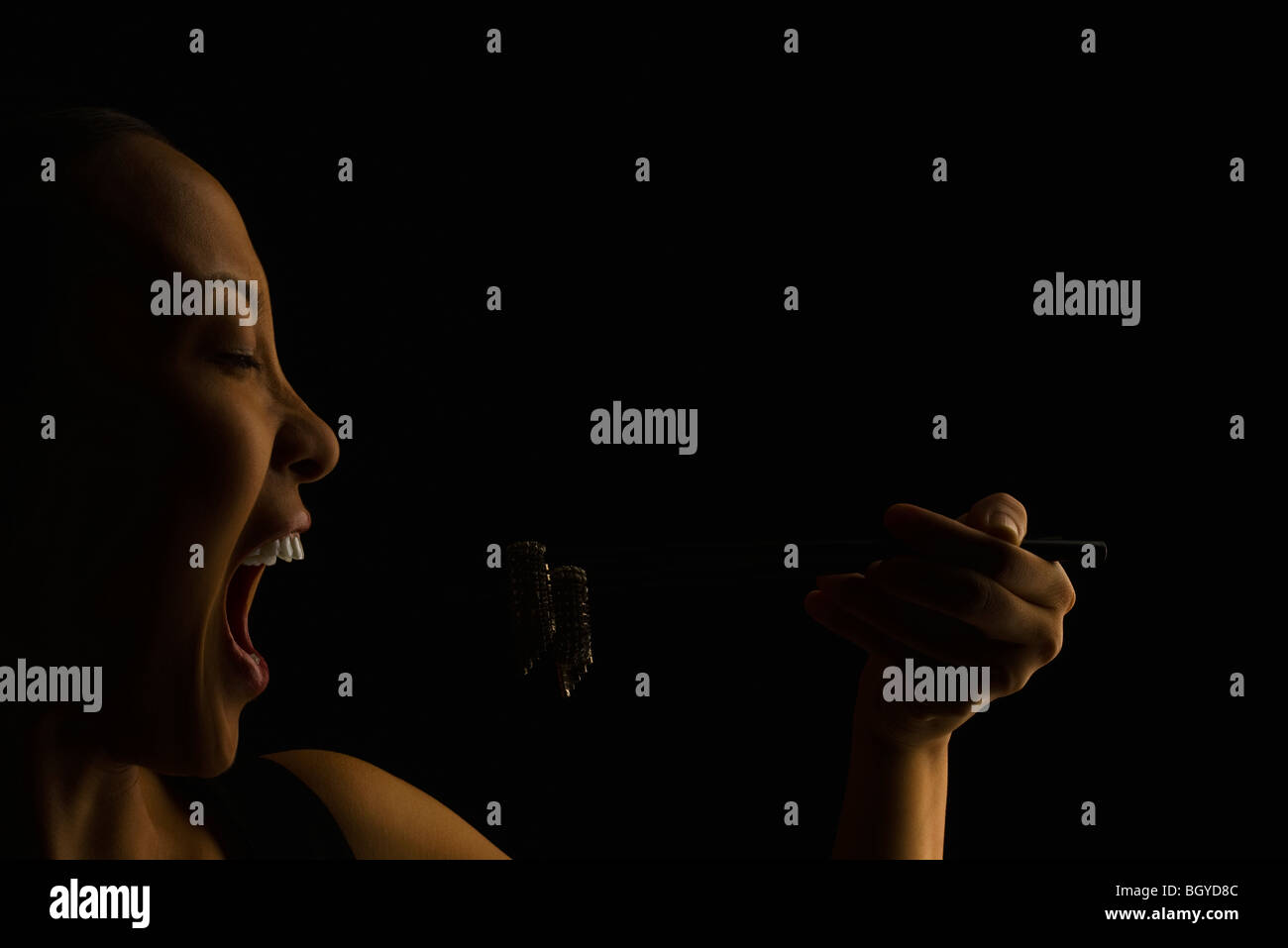 Jewelry indulgence, woman holding earrings to open mouth with chopsticks - Stock Image