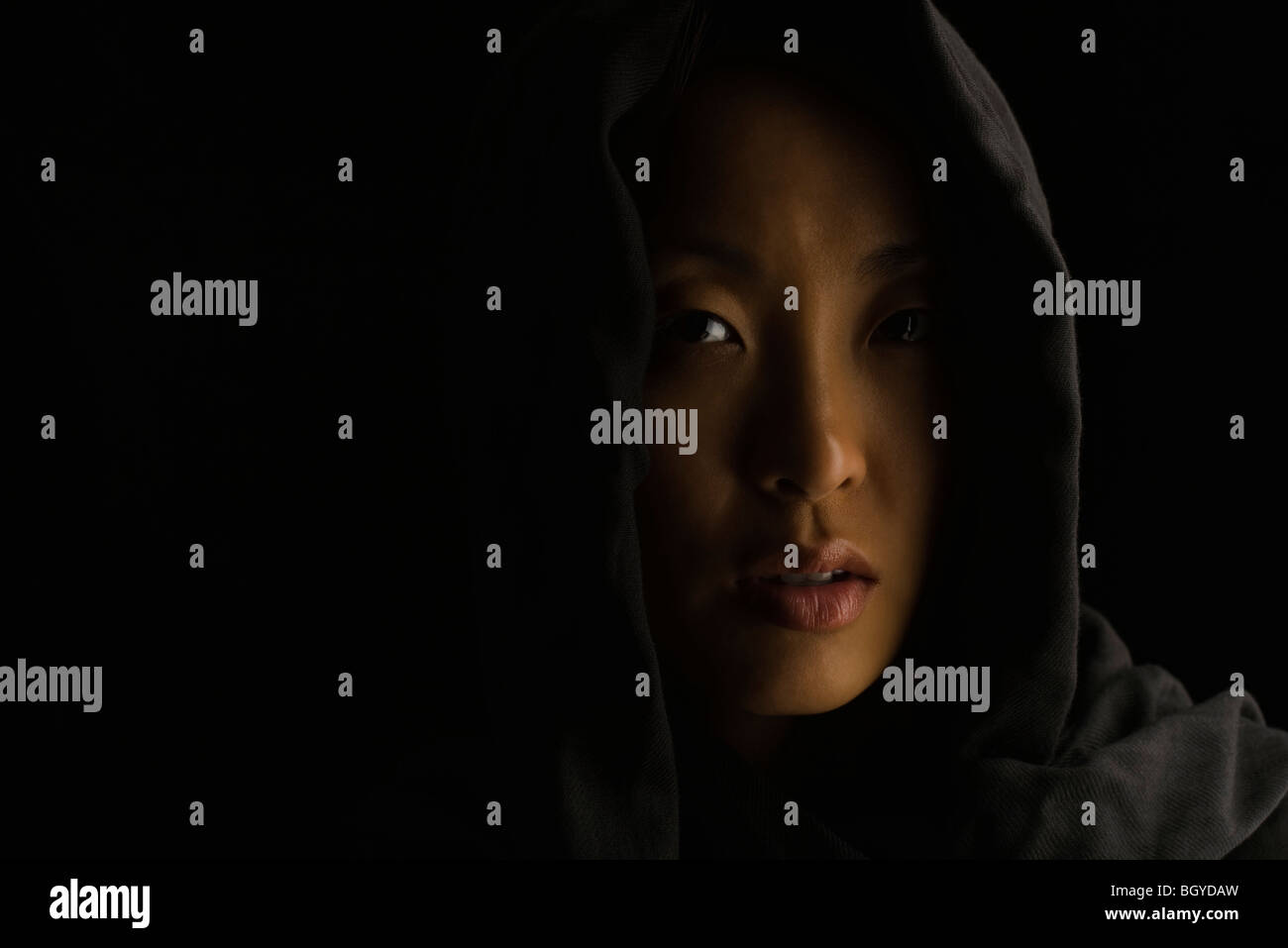 Woman wearing hood, looking apprehensively at camera - Stock Image