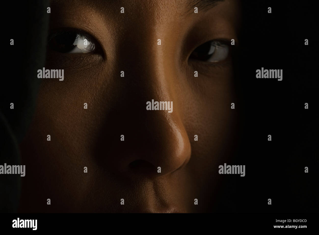 Woman looking mysteriously at camera, close-up - Stock Image
