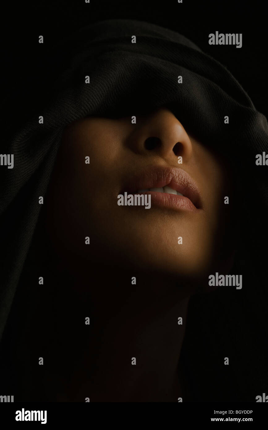 Woman with eyes concealed beneath hood - Stock Image