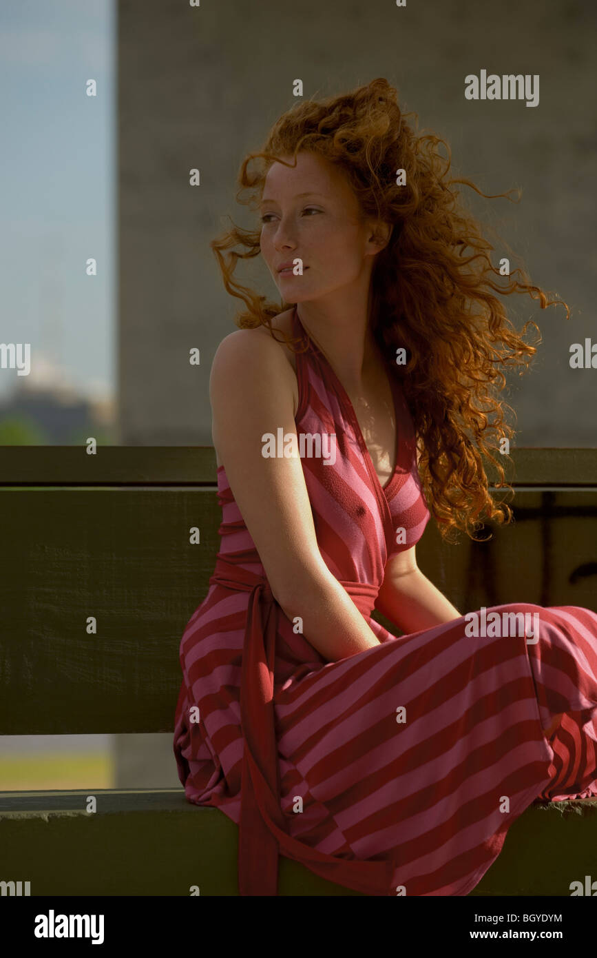 Young woman sitting outdoors, wearing dress, hair blowing in wind Stock Photo
