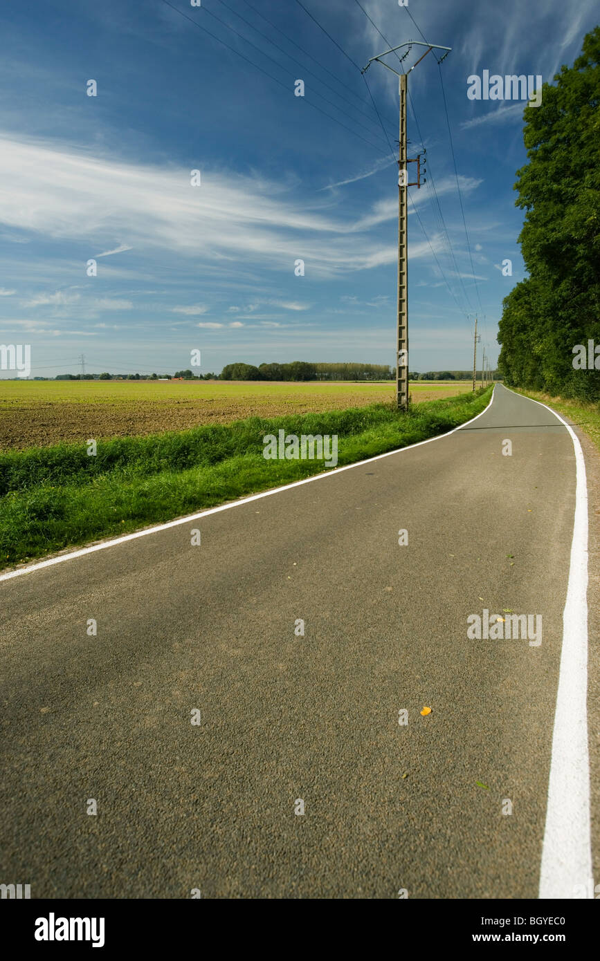 Country road winding past fields - Stock Image