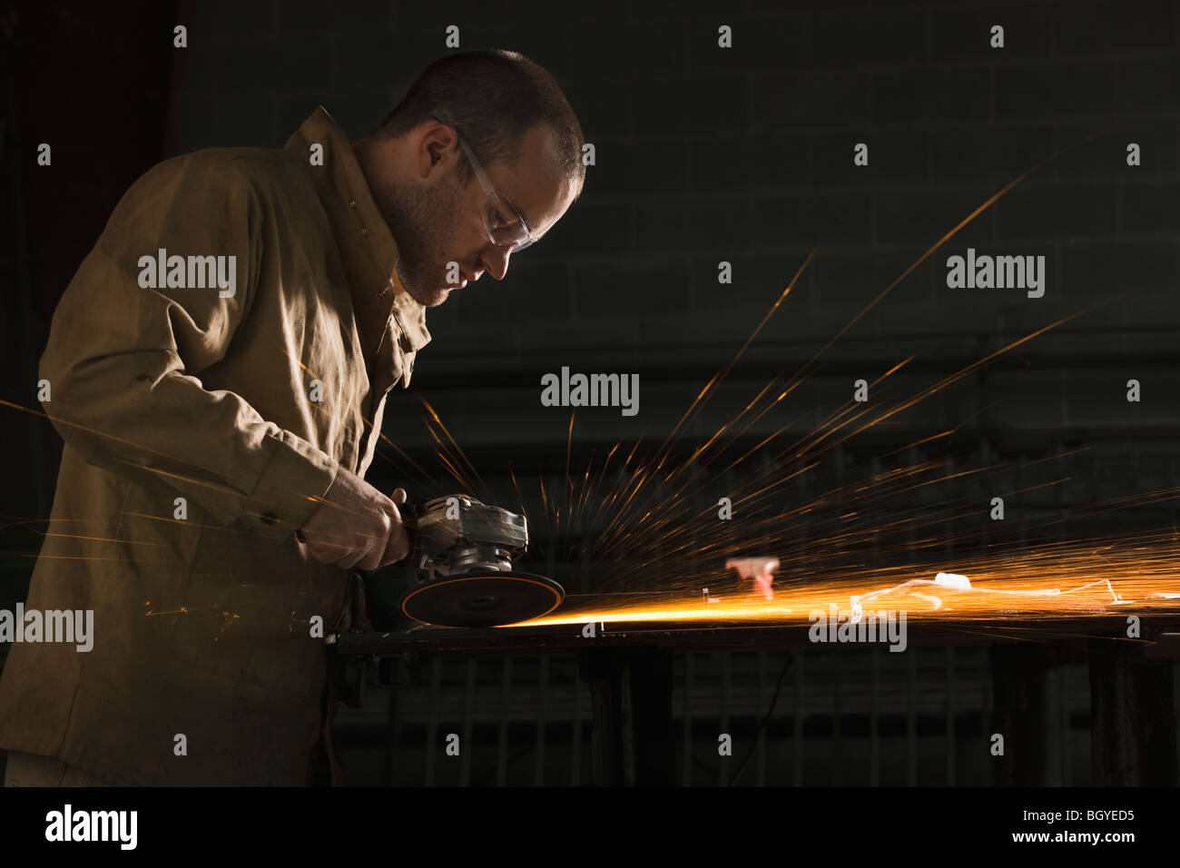 Steel grinder working in metal shop - Stock Image