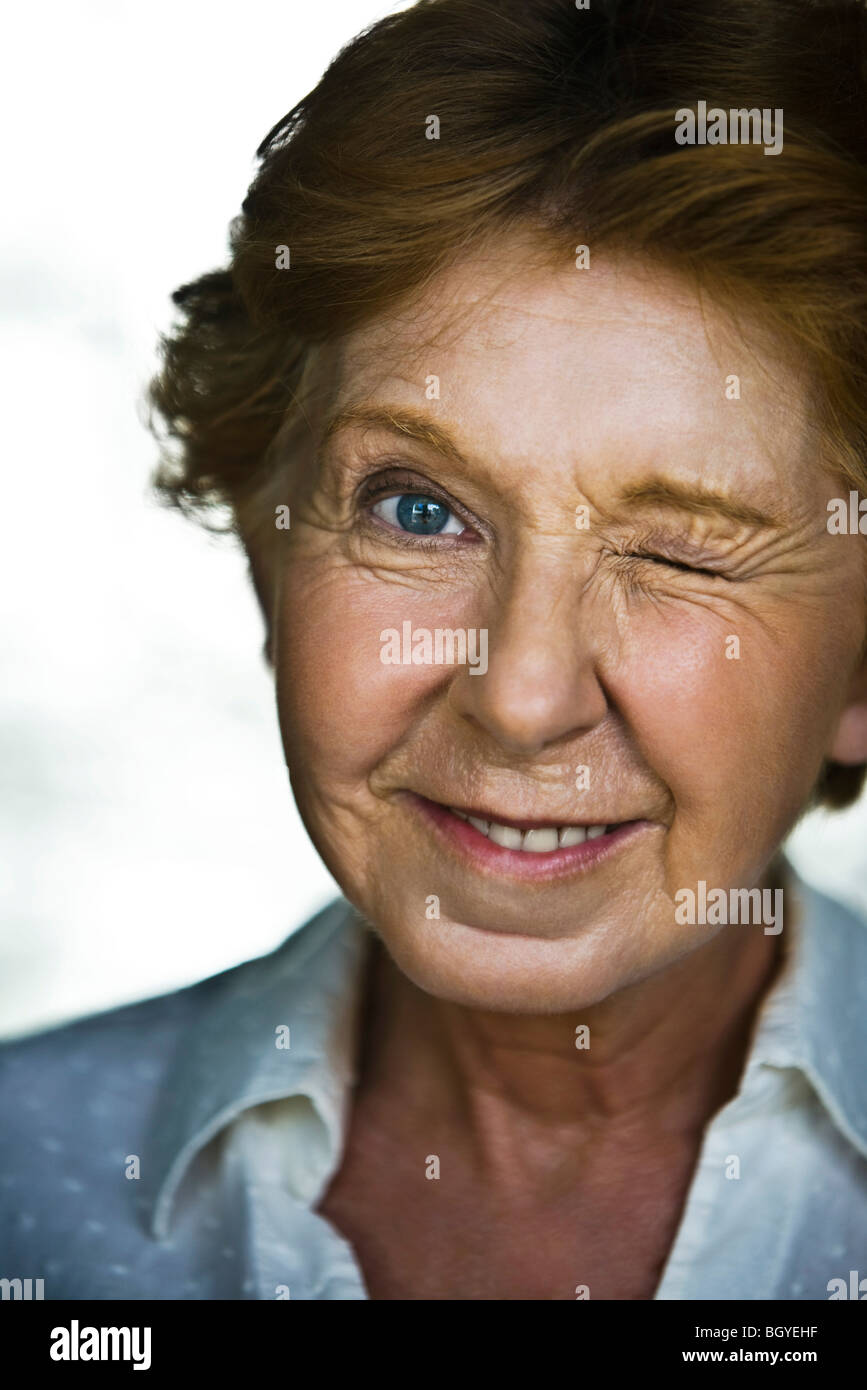 Senior woman winking, portrait - Stock Image