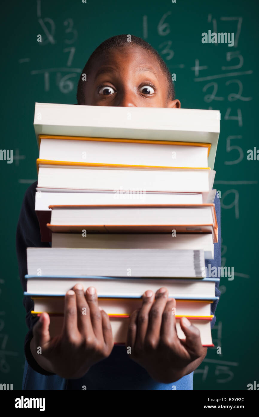 Boy holding stack of books - Stock Image