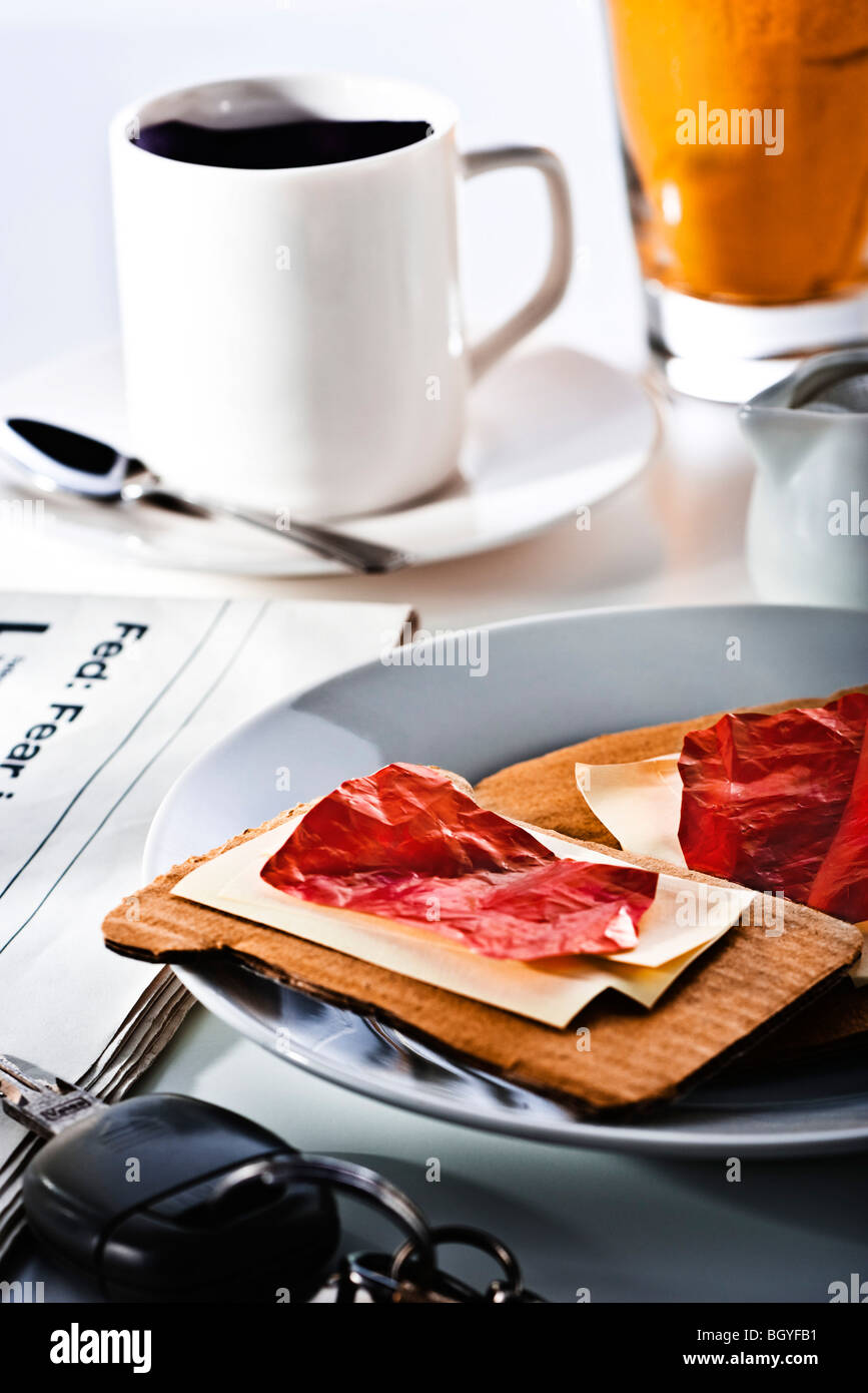 Food concept, fake breakfast constructed from paper and cardboard, newspaper and keys nearby - Stock Image