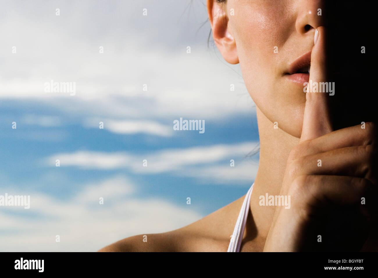 Woman holding finger on lips in silent gesture, cropped - Stock Image