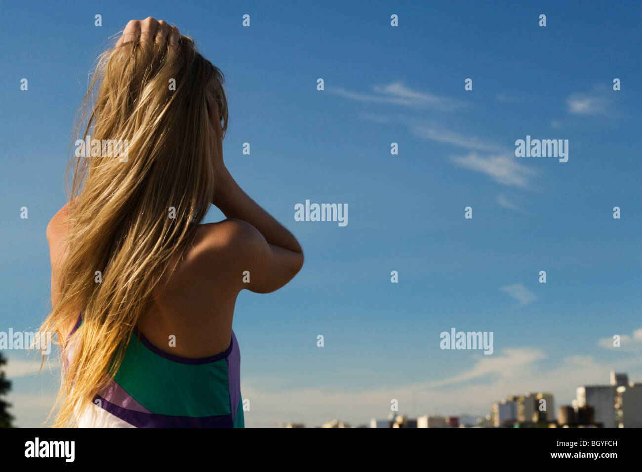 Female standing with hands in hair, looking at city in distance - Stock Image