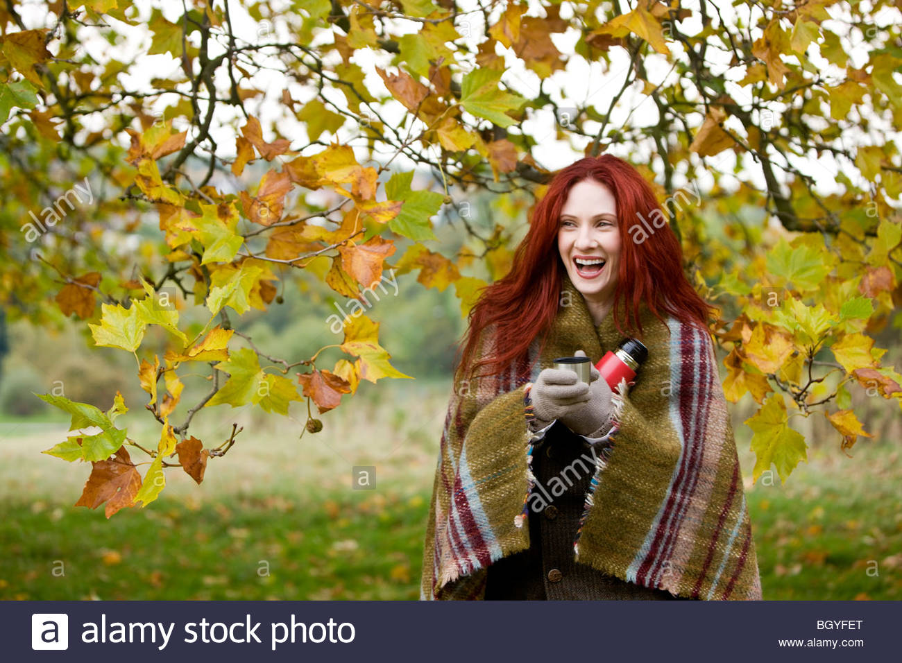 A young woman holding a flask, laughing - Stock Image