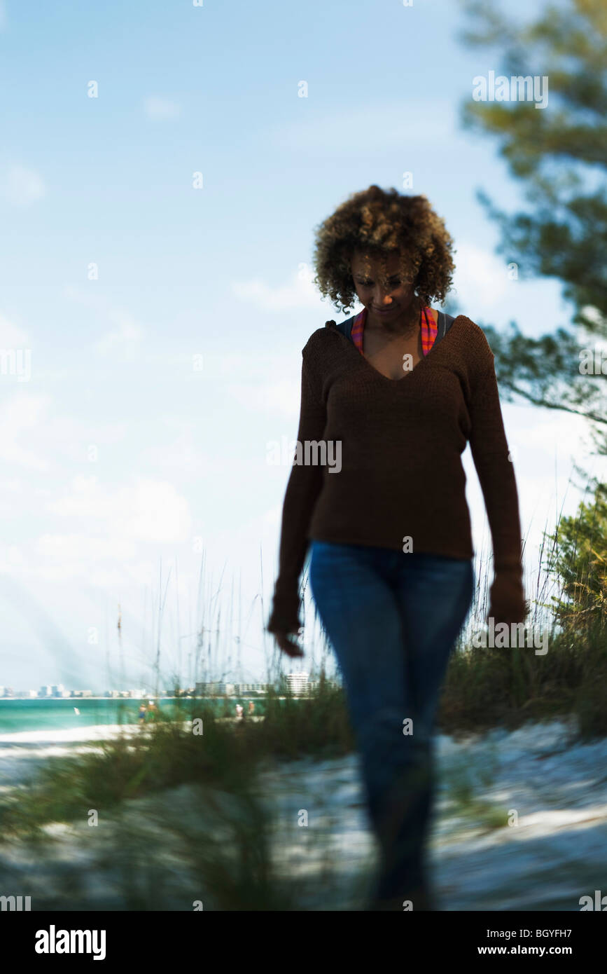 Woman walking at beach, dressed in casual clothing - Stock Image
